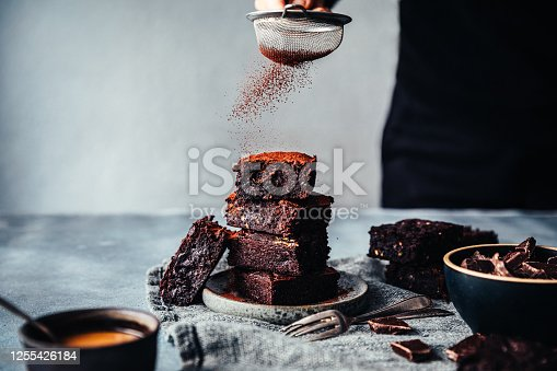Close-up of a woman hands sifting cocoa powder on cucumber brownies. Female preparing vegan cucumber brownies in kitchen.