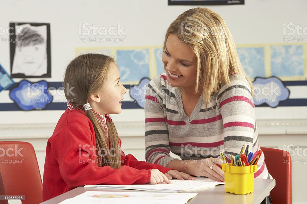 Female Primary School Pupil And Teacher Working At Desk royalty-free stock photo