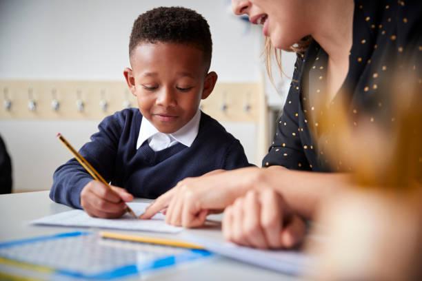maestro de escuela primaria femenino ayudando a un niño de escuela joven sentado a la mesa en un salón de clases, cerrar, enfoque selectivo - escuela primaria fotografías e imágenes de stock