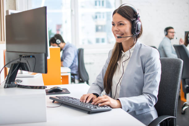 Female professional call center telesales agent wear wireless headset using computer in customer care support service office with team. stock photo