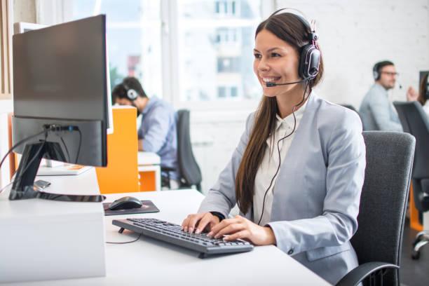 Weibliche professionelle Call-Center-Telesales-Agent tragen drahtlose Headset mit Computer in Kundenservice-Service-Büro mit Team. – Foto