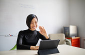 Businesswoman working in office, doing a video call with digital tablet. Female professional working in office and making a video call.
