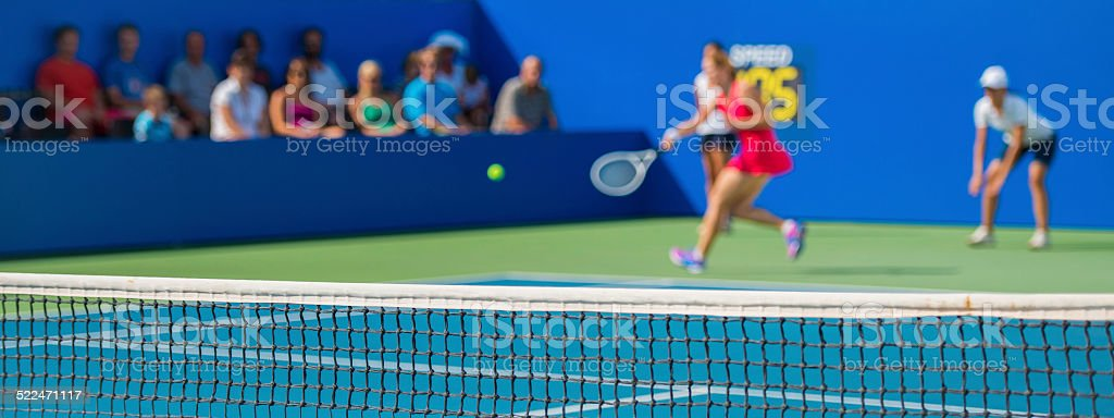 Female tennis player hitting a forehand in mid-air, with spectators...