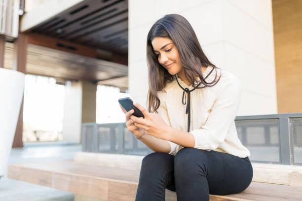 vrouwelijke professional met behulp van mobiele telefoon op bank - business woman phone stockfoto's en -beelden