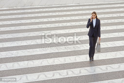 High angle view of female professional using smart phone on crosswalk. Full length of businesswoman is walking on street. Executive is in city.