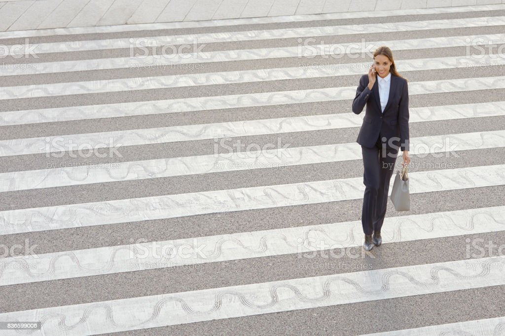female professional using smart phone on crosswalk stock photo