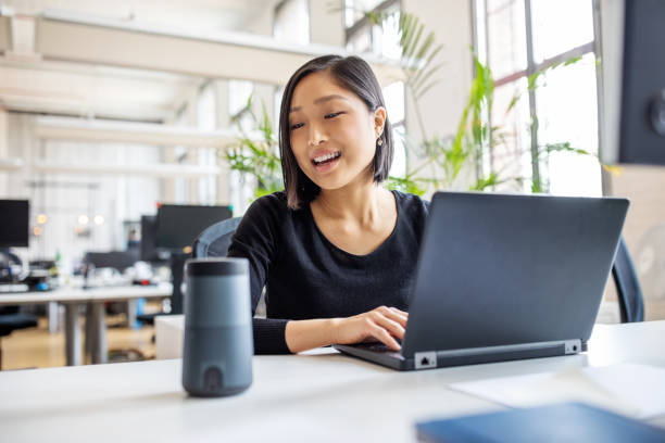 Female professional using virtual assistant at desk Asian businesswoman talking to virtual assistant at her desk. Female professional working on laptop and talking into a speaker. business laptop stock pictures, royalty-free photos & images