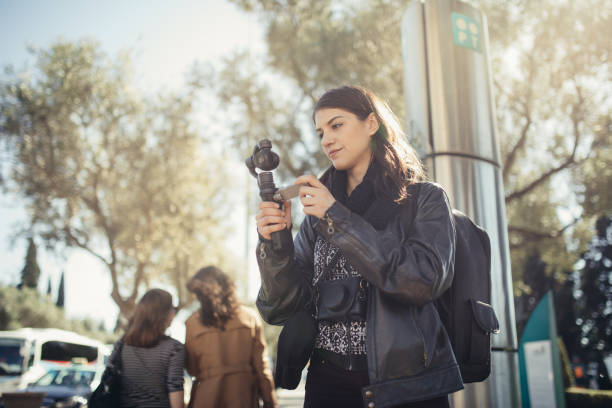 Female professional videographer travel photographer making video in 4K resolution trough of the streets holding 3 axis gimbal stabilizer stock photo