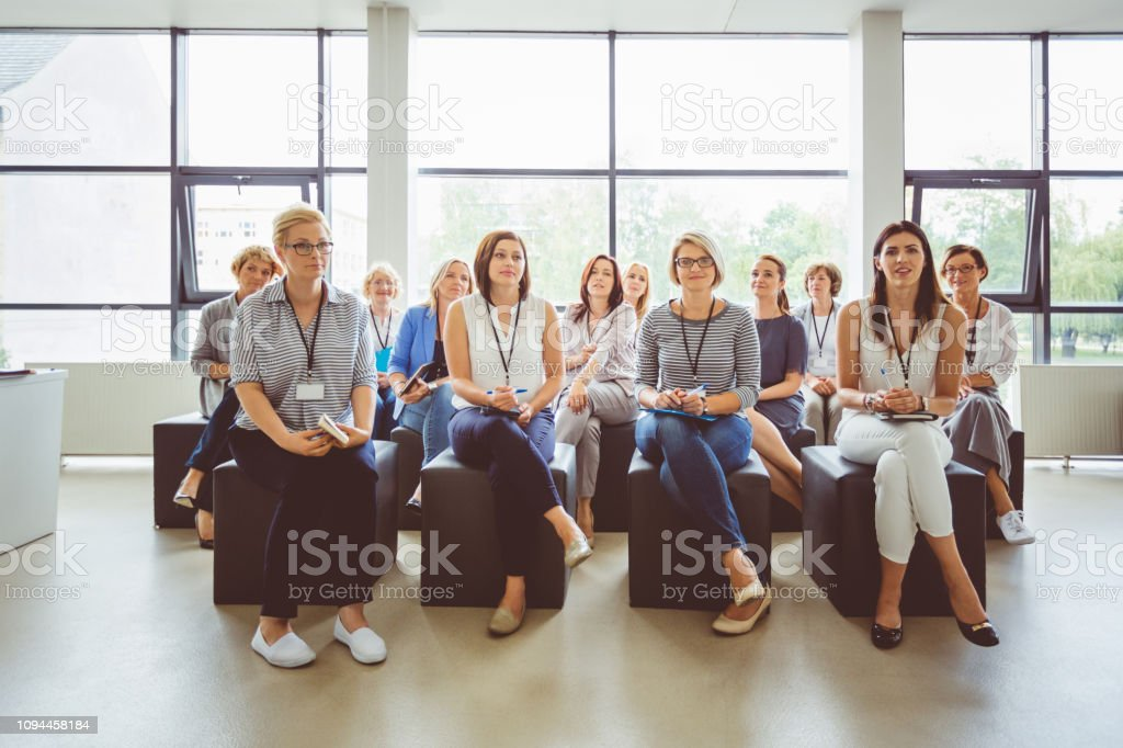 Female professionals attending a seminar Group of female business professionals attending a seminar. Women sitting in a conference hall during a training programme. Adult Stock Photo