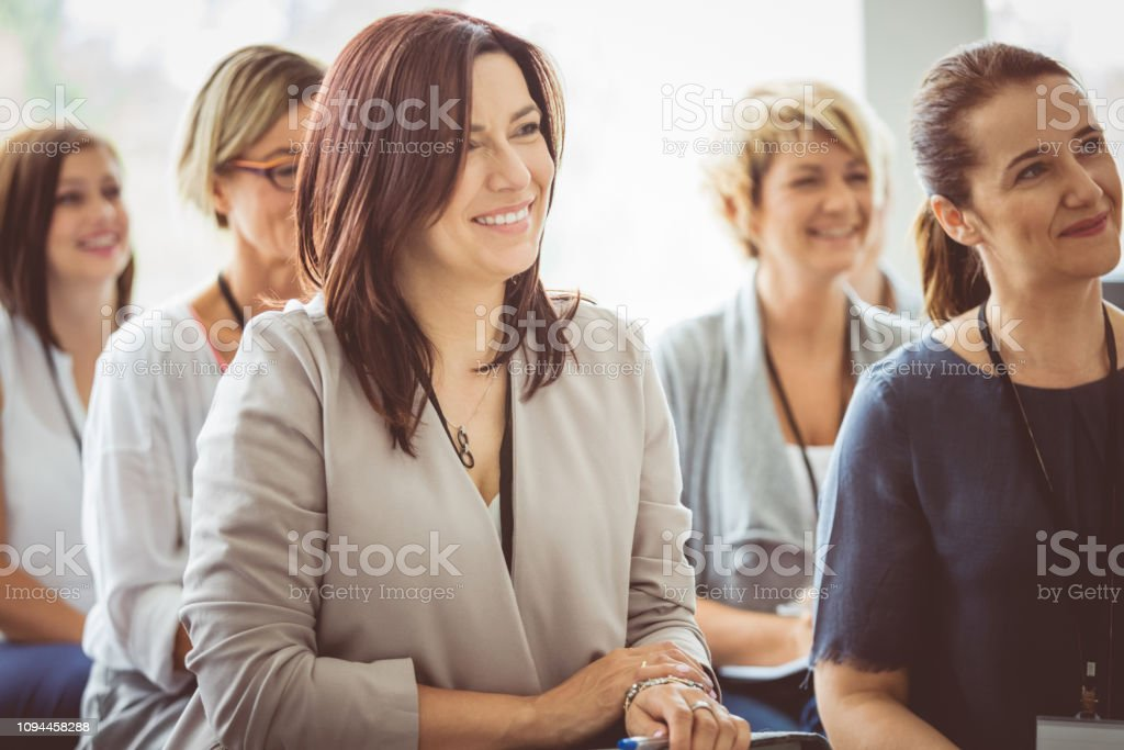 Female professionals attending a seminar Smiling mature woman sitting in audience and listening to the speaker. Female business professionals attending a seminar. Adult Stock Photo