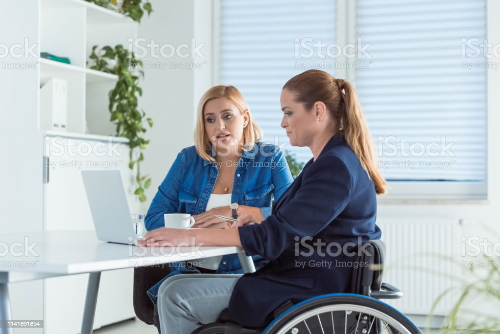 Female professionals using laptop at desk Female professionals using laptop at desk. Disable businesswoman is working with colleague in start-up office. They are working on new business plans. 40-44 Years Stock Photo