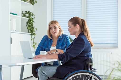 Female Professionals Using Laptop At Desk Stock Photo - Download Image Now