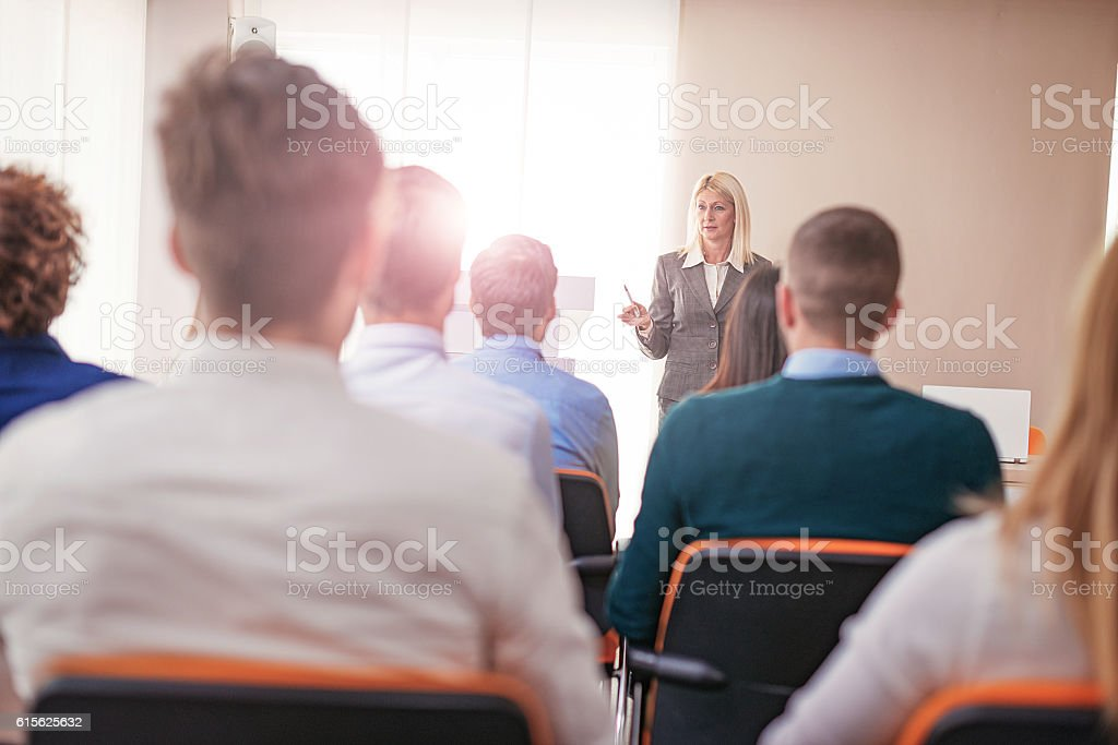 Female professor at faculty class, having discussion with students stock photo
