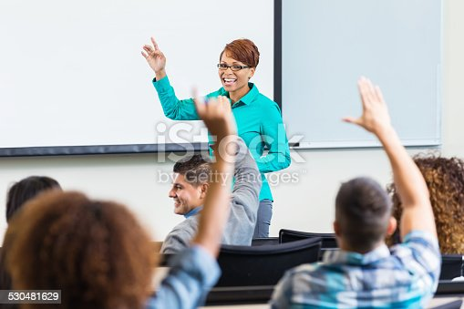 600055398 istock photo Female professor taking questions after lecture in college classroom 530481629