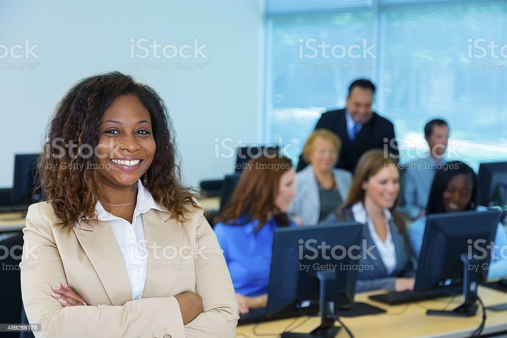 Female professor with computer lab students stock photo