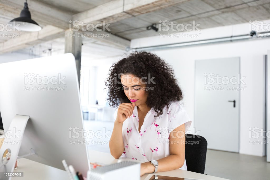 Female programmer working at her desk in office Female programmer working at her desk in office. Mixed race woman thinking while working at modern office. Adult Stock Photo