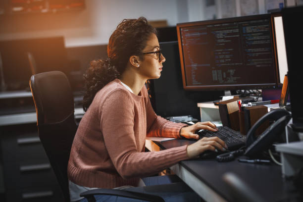 Female programmer working on new project. Female programmer working on new project.She working late at night in her office. software developer stock pictures, royalty-free photos & images