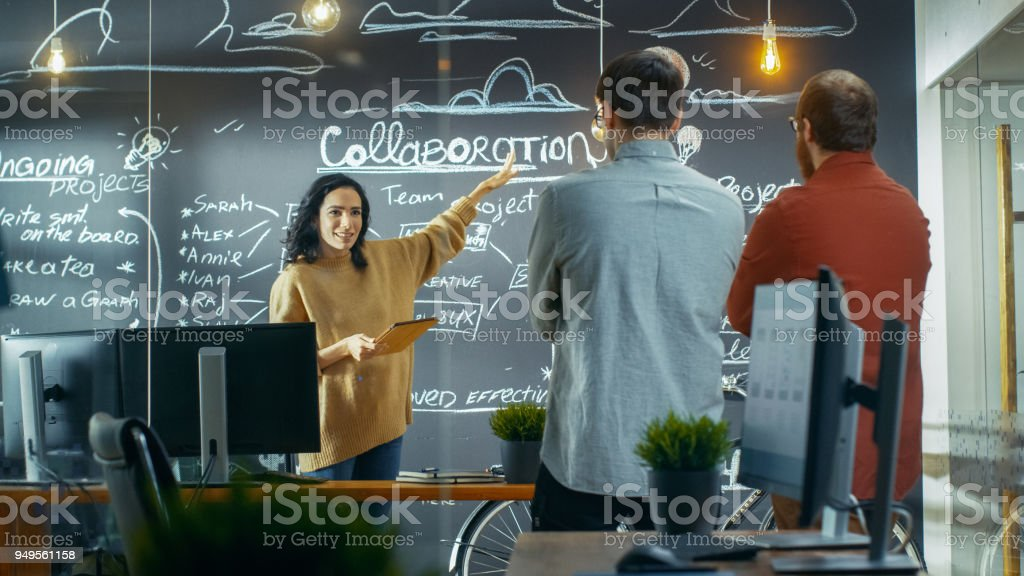 Female Project Manager Holds a Meeting with Her Coworkers, She Holds Tablet Computer and Shows Her Plan Drawning a Blackboard Wall. They Work in the Creative Agency. stock photo