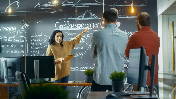 weiblich-projekt-manager hält ein treffen mit ihren kollegen, sie trägt tablet-computer und zeigt ihr plan zeichnungen eine blackboard-wand. sie arbeiten in der kreativagentur. - projektmanager stock-fotos und bilder