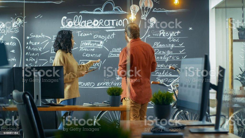 女性プロジェクト マネージャーを保持しているタブレット コンピューターやショーを計画描かれた男性開発者に黒板の壁に。彼らは創造的な機関で働きます。 ストックフォト