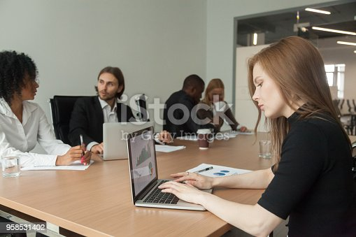 istock Female project manager working on laptop at meeting analyzing statistics 958531402