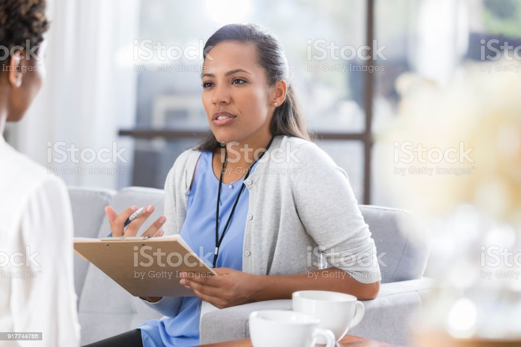 Female psychiatrist discusses something with female patient stock photo