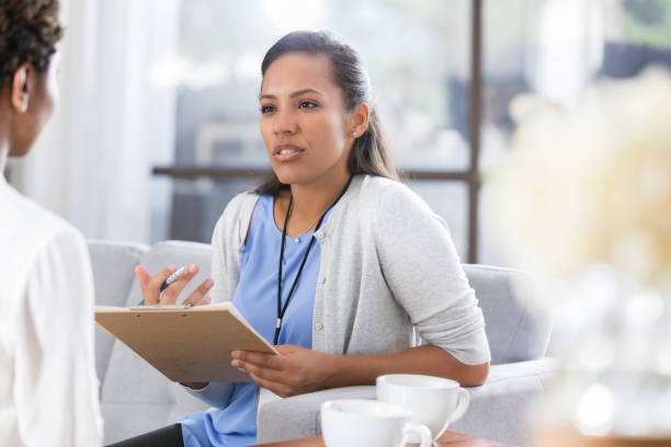 female psychiatrist discusses something with female patient - psychiatrist stock photos and pictures