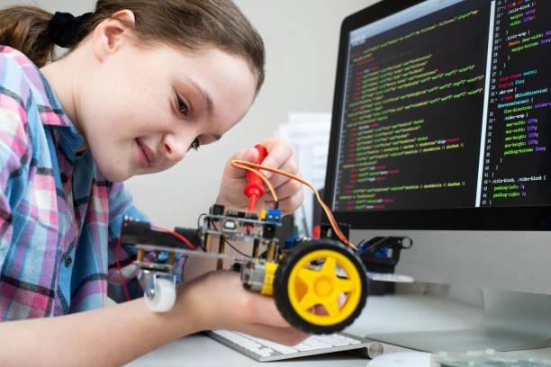 alumna mujer edificio coche robótico en la lección de ciencias - robótica fotografías e imágenes de stock