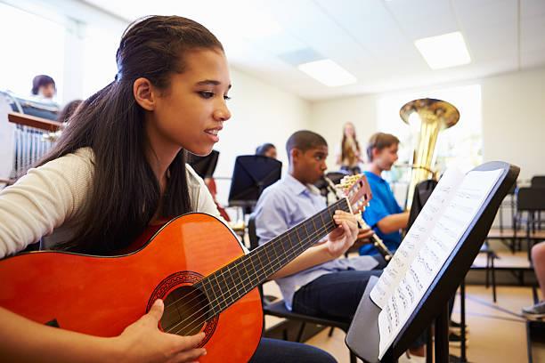 Weibliche Schüler spielen Gitarre In der High School Orchestra – Foto