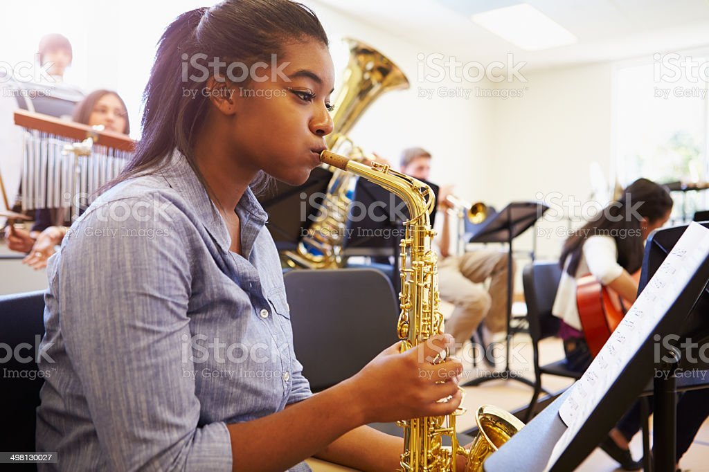 Female Pupil Playing Saxophone In High School Orchestra royalty-free stock photo
