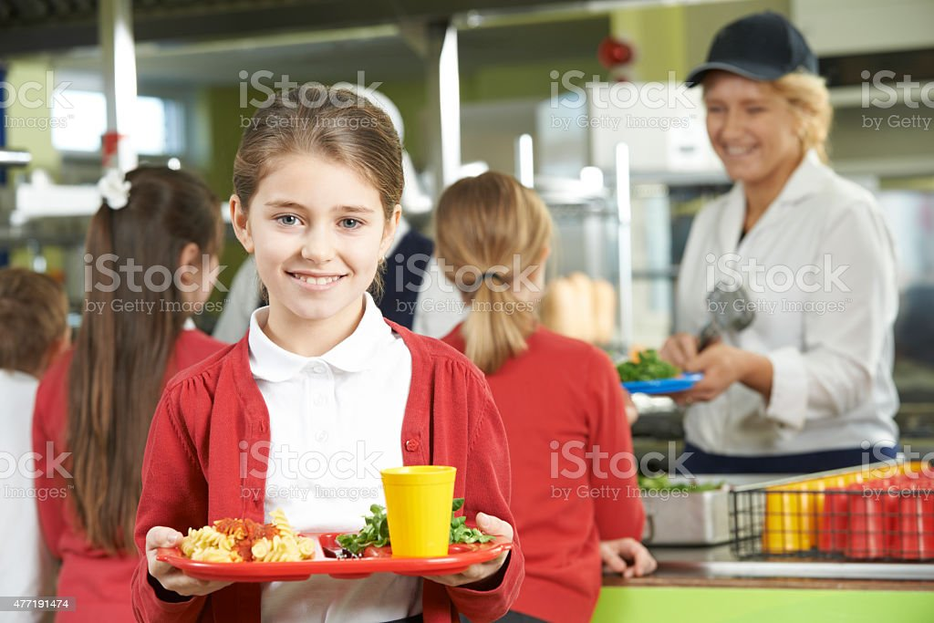 Female Pupil With Healthy Lunch In School Cafeteria stock photo