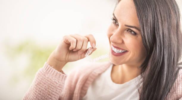 Female putting invisiline braces on while smiling. stock photo