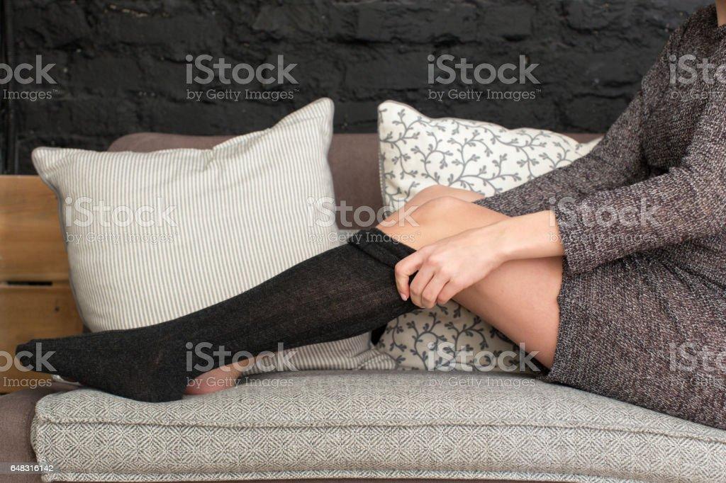 Female putting on black stockings stock photo