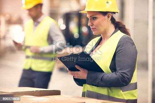 Female manager in reflective vest and hardhat looking at packages and taking notes in her clipboard.