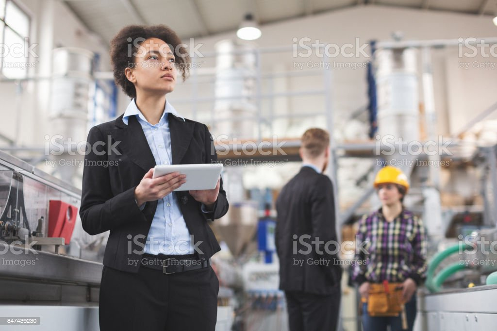 Female quality inspector using tablet pc at factory stock photo