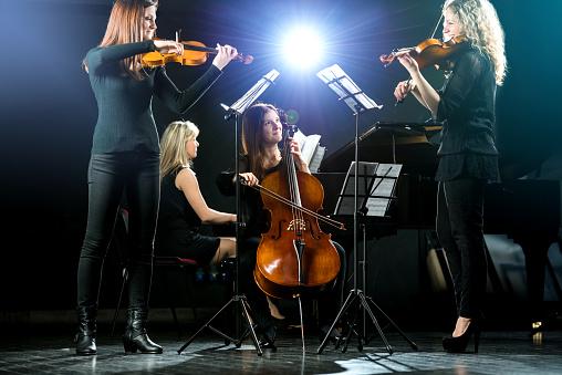 Female quartet playing music a rehearsal.