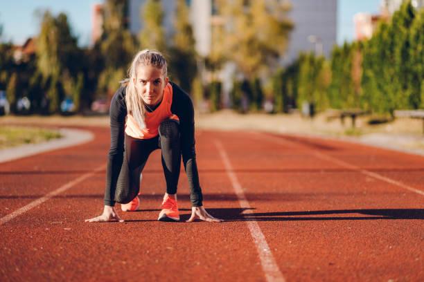 läuferin auf einer rennstrecke - joggerin stock-fotos und bilder