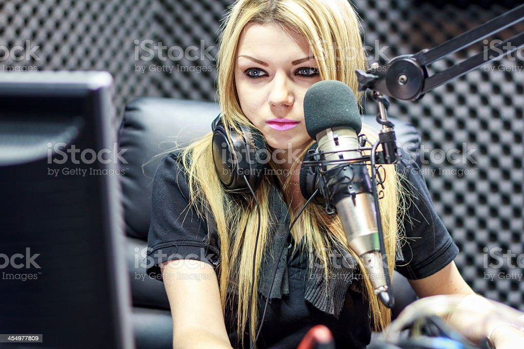 Female radio DJ looking at computer screen stock photo