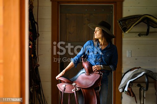 Female farmer in a tacking room. Rancher working on a Canadian ranch. Empowered woman working in agriculture.
