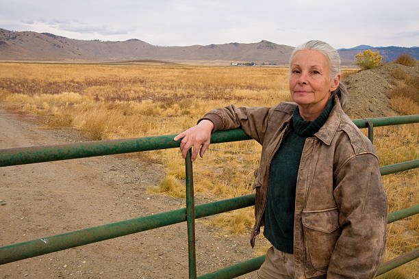 female rancher senior female rancher standing at gate for last time rancher stock pictures, royalty-free photos & images