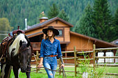 Female farmer working with horses. Rancher working on a Canadian ranch. Empowered woman working in agriculture.
