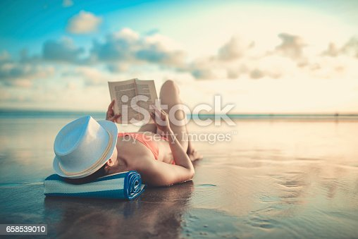 Female Reading book and Enjoying Sunset on Beach by the Ocean