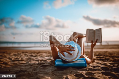 istock Female Reading and Enjoying Sunset on Beach by the Ocean 933846814