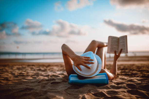 Female Reading and Enjoying Sunset on Beach by the Ocean stock photo