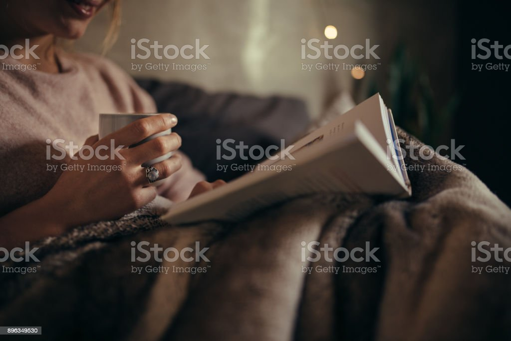 Female reading book on bed at night