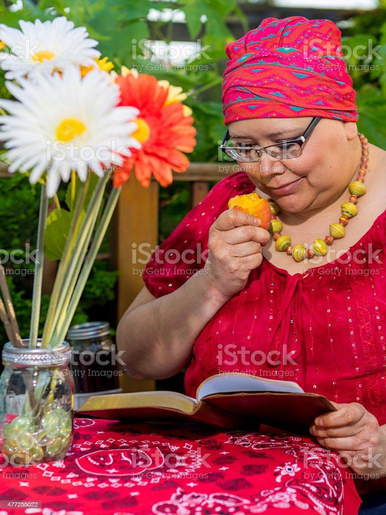 Female Reading Outdoors On Patio stock photo