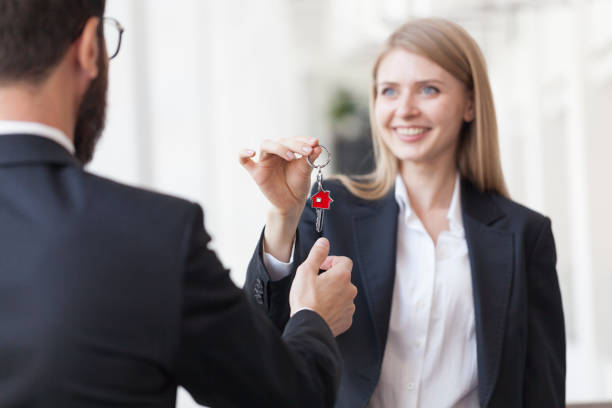 Female Real estate agent giving keys to customer stock photo