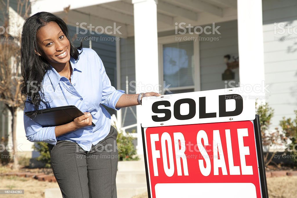 Female Real Estate Agent Holding Sold Sign Outside Home stock photo