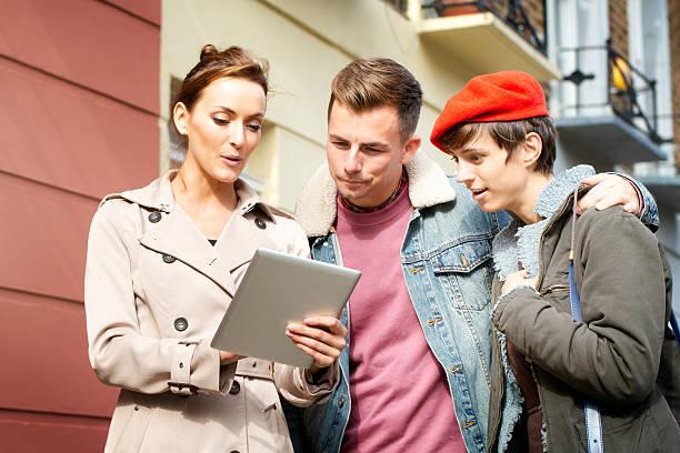 weibliche immobilienmakler pitching hotel zu paar mit tablet - frisch verheirateten beratung stock-fotos und bilder