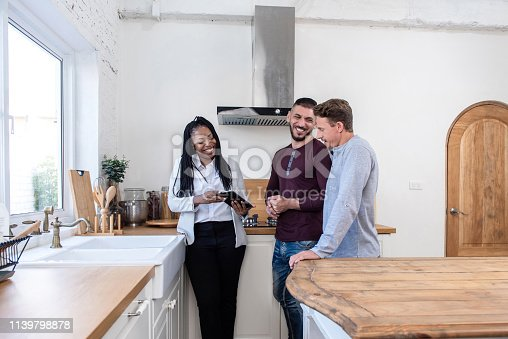 istock Female real estate agent showing gay couple around new house 1139798878